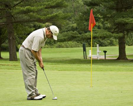 Man on green putting golf ball toward red flag. Stock Photo