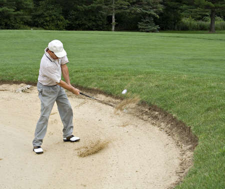 Sand and ball can be seen flying as golfer hits from sand trap.l photo