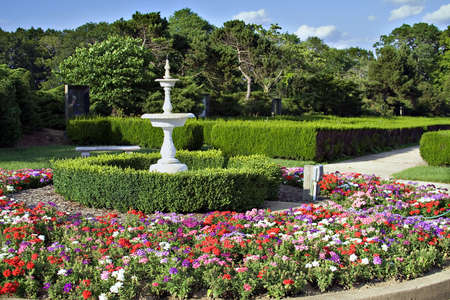 Highly saturated garden scene.  Fountain, hedges, flowers Stock Photo