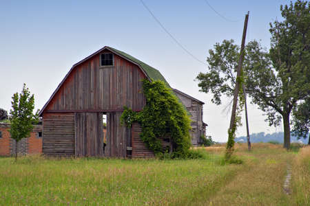 Old abandoned farm  - barn foreground, house in background. Stock Photo
