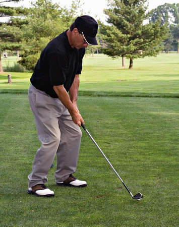 Man addressing the golf ball - black hat, black shirt - professional that knows how to golf.