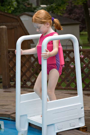 Small red-haired girl wearing a safety swimsuit entering backyard swimming pool. Stock Photo - 482154