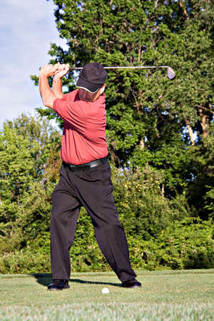 Golfer winding up to hit the ball. photo