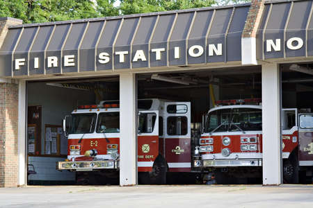 estacion de bomberos: Una ciudad la estaci�n de bomberos - las puertas abiertas y camiones en espera. Foto de archivo