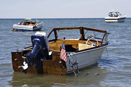 A 1963 Henry outboard with Evenrude motor, anchored off shore of Lake Erie, Cleveland Ohio. photo
