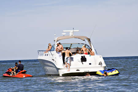 A large luxury boat full of people enjoying a summer weekend on the lake.