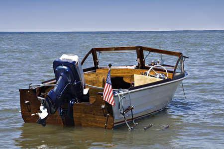 henry: A 1963 Henry outboard with Evenrude motor, anchored off shore of Lake Erie, Cleveland Ohio.