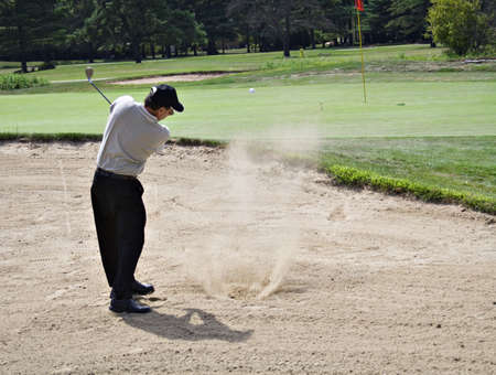 boogie: Action shot of golfer hitting ball from sand trap.  Sand splash and ball visible above green.