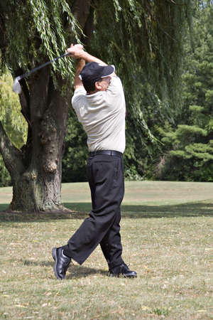 wispy: Golfer with club in back swing after drive completed.  Wispy willows in background.