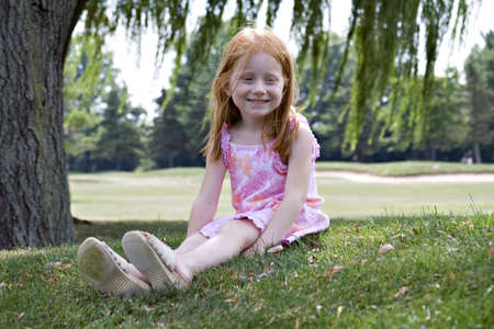 Small redhaired girl sitting under a willow tree in summertime. Stock Photo - 521832