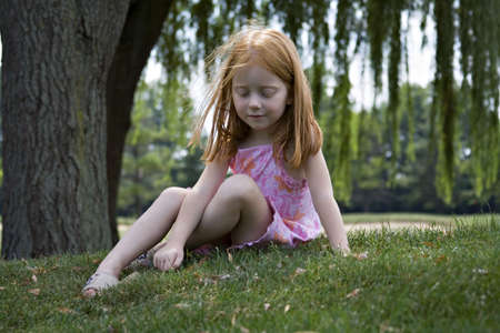 Small girl sitting under willow tree playing with grass. Stock Photo - 521836
