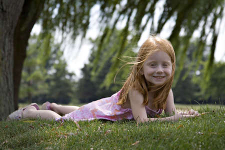 Small red-haired girl laying in the grass under willow trees. photo