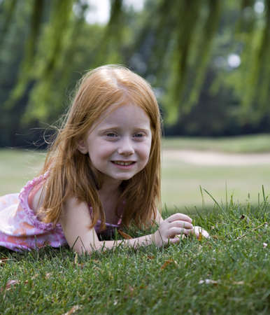 Small red-haired girl enjoying a summer day playing under willow tree. Stock Photo - 521841