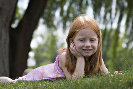 Small redheaded girl laying in grass contemplating the world around her. Stock Photo - 521838