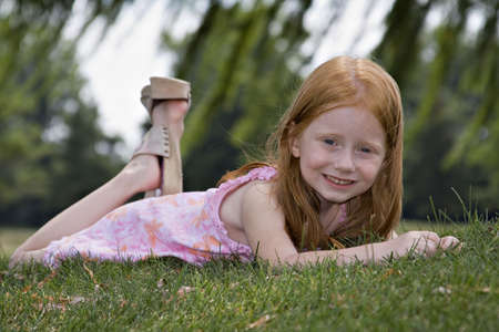 Red-haired girl laying in the grass. Stock Photo - 521839