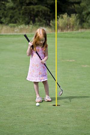 Roja pequeña niña de cabello tratando de conseguir la pelota de golf en el agujero. Foto de archivo - 521843