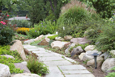 Beautiful path through a cottage type garden.  House rooftop visible in distance. Stock Photo