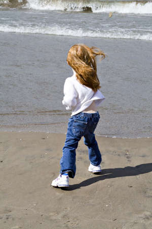 Small red read girl throws rocks into the lake on a windy day. Stock Photo - 547110