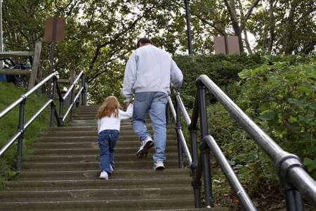 climbing stairs: Abuelo ni�o caminando hasta escaleras concretas en un parque.