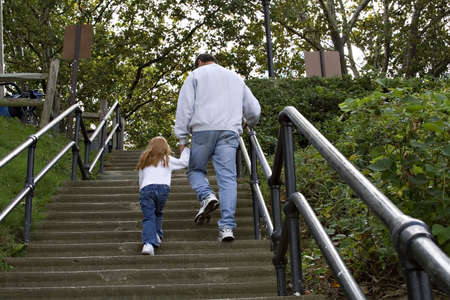 Grandfather walking child up concrete stairs at a park.