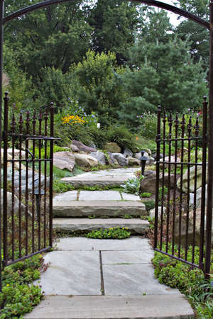 The  black wrought-iron garden gate entrance to an enchanted, peaceful flower garden.