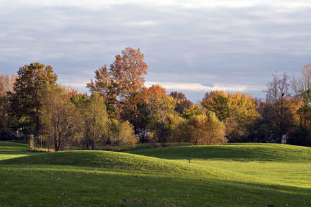 An impressive sky - clouds rolling in illuminated by a setting sun.  Trees in autumn colors glow. Scenic golf course.