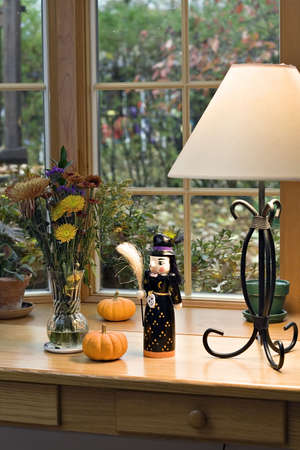 sill: A table decorated with halloween and fall decorations.  Pumpkins, witch, and vase of flowers.  Leaves and fall day visible through window.