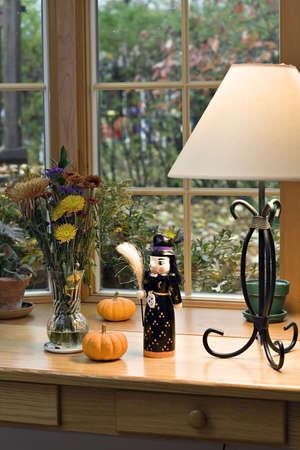 Een tabel versierd met Halloween en vallen decoraties. Pompoenen, heks, en de vaas met bloemen. Bladeren en vallen dag zichtbaar door venster.