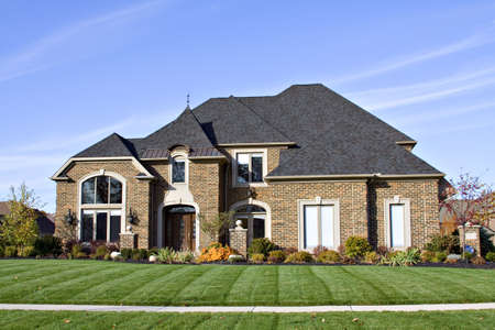 housing lot: A large American brick home with many roof angles and windows.