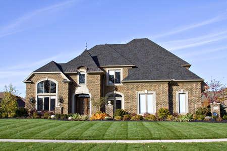 mediaan: Een grote Amerikaanse bakstenen huis met veel hoeken dak en ramen.