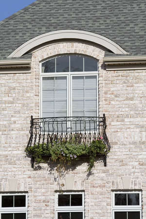 A upscale American Home in Ohio.  Balcony with trailing flowers adorne a window. photo