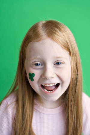 Redheaded girl with a shamrock painted on her cheek - smiling Irish eyes. photo
