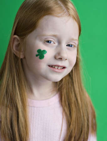 A very young red-haired girl with green shamrock painted on her face for St. Patricks Day. photo