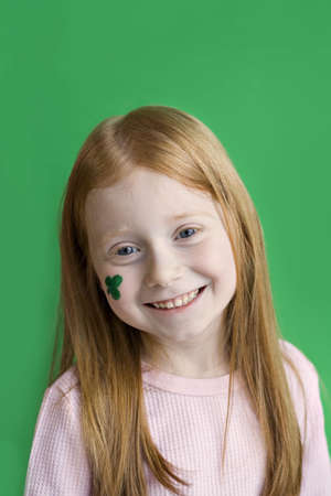 A smiling red-headed girl with green shamrock on her cheek for St. Patricks Day celebration. Stock Photo