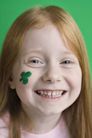 I smiling girl with green shamrock on her cheek anticipates St. Patricks Day celebrations.