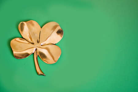 fourleaf: A gold four-leaf clover on a green background. Stock Photo