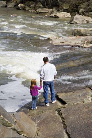 川の端に手を繋いでいる彼の孫娘との祖父。