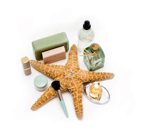A grouping of various perfumes, cosmetics and soaps surrounding a starfish on white.