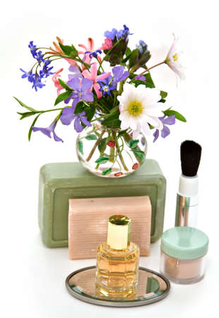 grouping: A grouping of cosmetics, perfume, soap with spring flowers isolated on white.