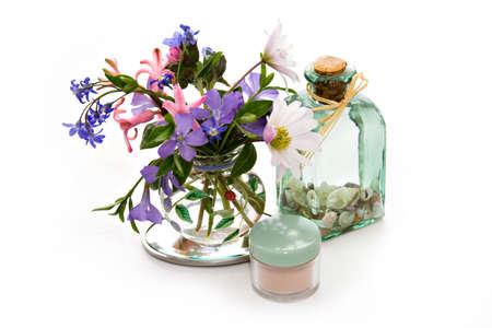minature: Beauty products with a mix of minature sea shells and flowers isolated on white.