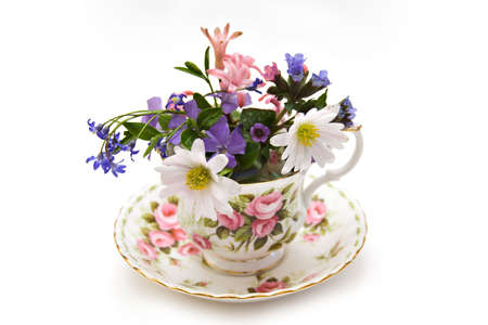 sof: A bone china teacup and saucer filled with spring flowers - isolated on white - shallow depth of field.
