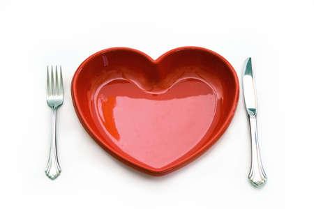 Een houtkachel gezondheid concept - geïsoleerd op wit - rood hart bord, mes en vork.