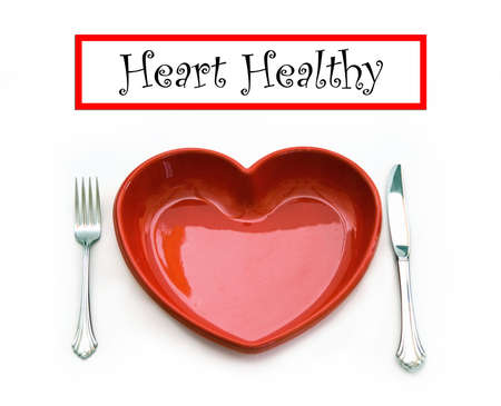 A heart health concept - isolated on white - red heart plate, knife and fork with text banner graphic. Stock Photo