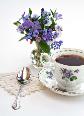 Spring flowers and a chine teacup, heart shaped doily shallow depth of field.