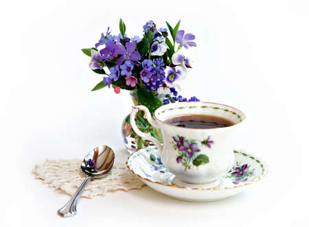 violets: A cup of tea - spoon on shaped doily - violets on cup and in flower arrangement. Stock Photo