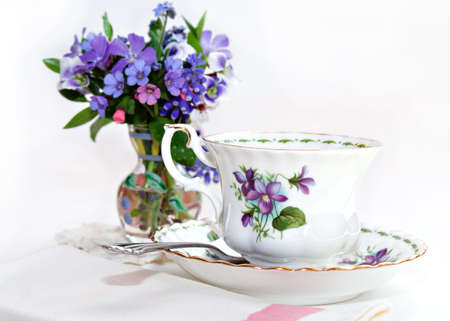 Teacup and vase of flowers - shallow depth of field Stock Photo