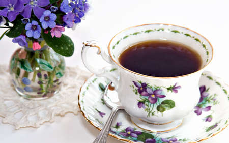 A bone chine cup of tea - - vase of flowers from the garden; shallow depth of field