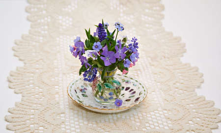 A small vase of spring flowers on saucer and lace doily.