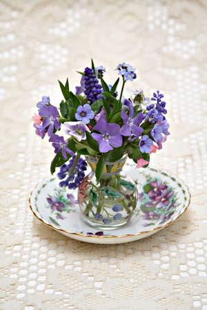 Small vase of spring flowers on saucer.  Lace runner ecru runner.