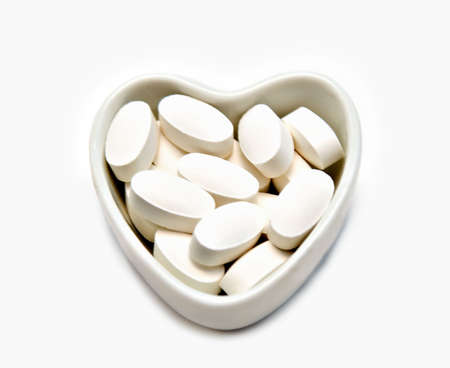 A heart-shaped dish filled with white pills.   Could be a concept for heart of E.D. medication